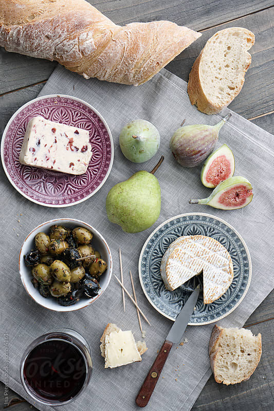 Cheese, red wine, fruits and bread by Ina Peters for Stocksy United