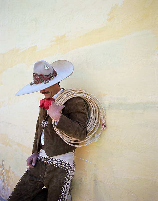 Mexican Cowboy leaning on wall with lasso. by Hugh Sitton for Stocksy United