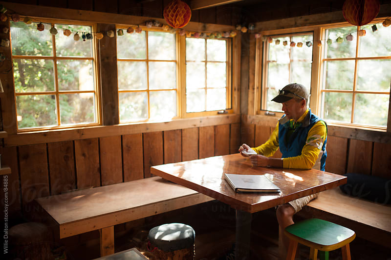 Man Sitting at Table in Cabin by Willie Dalton for Stocksy United