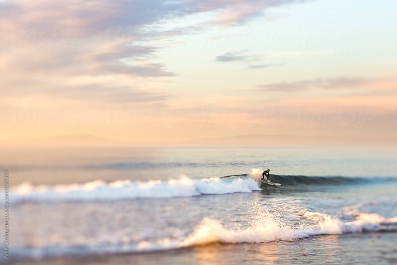 Surfer at sunset by Amy Covington for Stocksy United