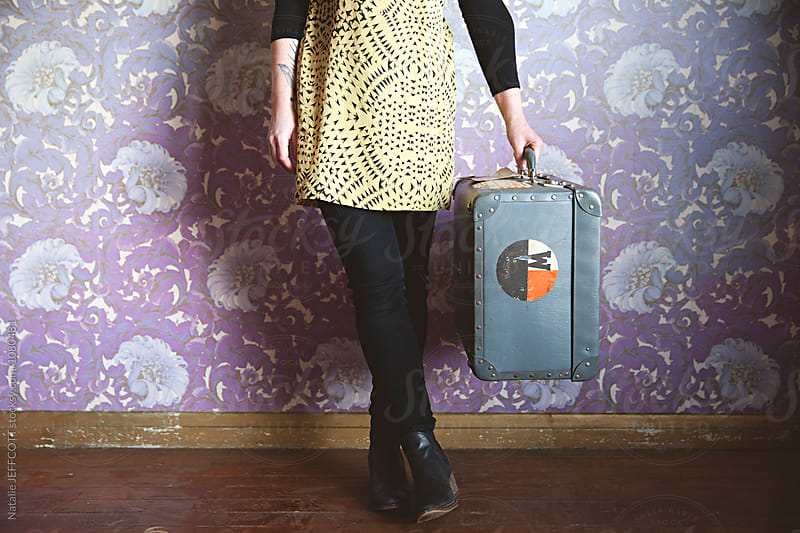 Anonymous female holding a vintage suitcase in front of retro wallpaper by Natalie JEFFCOTT for Stocksy United