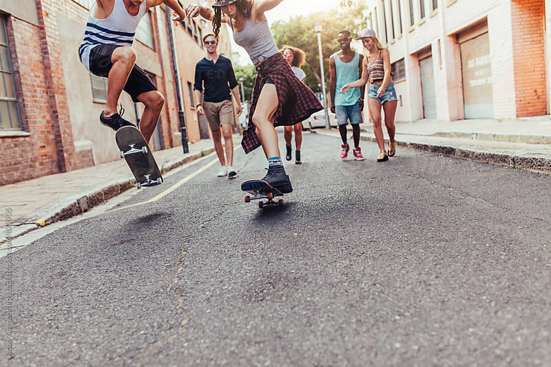 Young people walking and skating on city street by Jacob Ammentorp Lund for Stocksy United