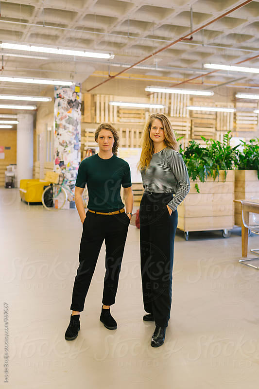 Two young women standing in their studio. by Ivo de Bruijn for Stocksy United