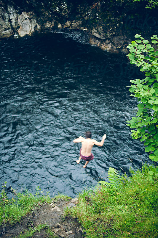 Young man jumps off a waterfall into the water by Denni Van Huis for Stocksy United