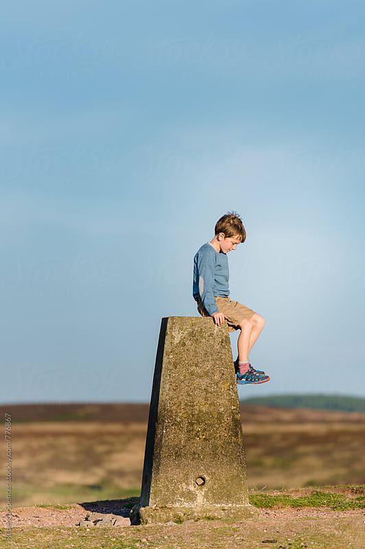 Child resting on a trig point pillar on top of the Quantock Hills in Somerset, England by Rebecca Spencer for Stocksy United