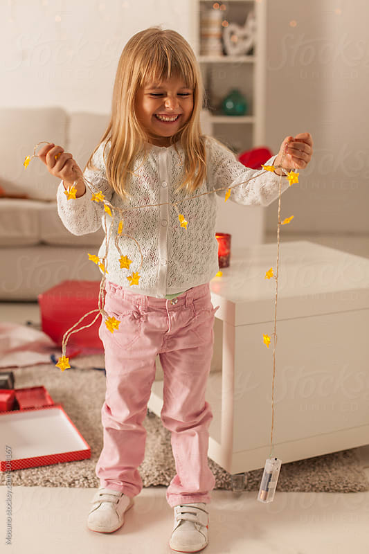 Cute Girl Holding Christmas Light Decoration by Mosuno for Stocksy United
