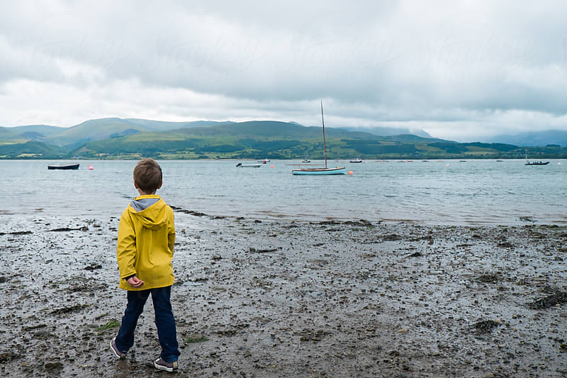 Little boy standing by the estuary by Léa Jones for Stocksy United
