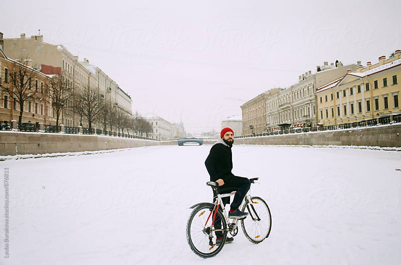 Man on bicycle in a riverbed by Lyuba Burakova for Stocksy United
