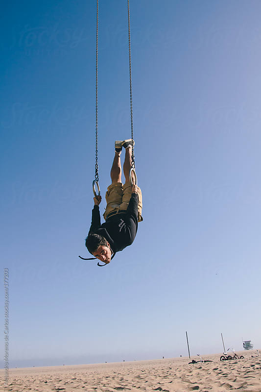 Young man upside down on gymnastic rings on the beach by Alejandro Moreno de Carlos for Stocksy United