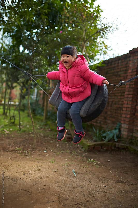 one happy girl on swing by Bo Bo for Stocksy United