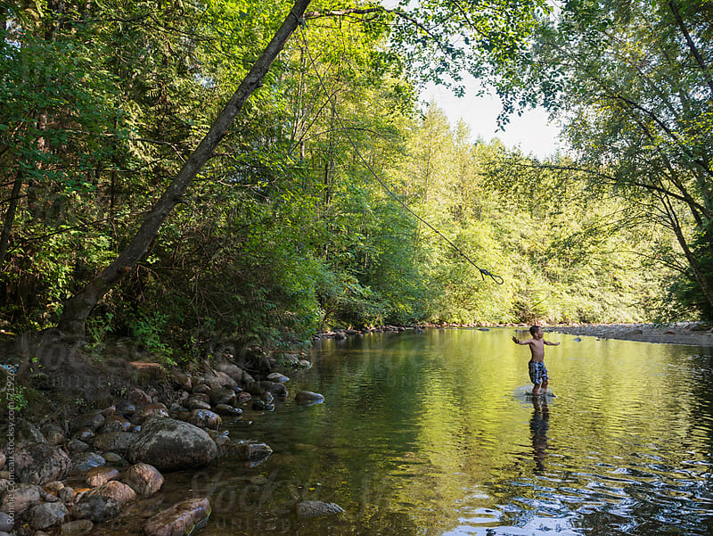 Boy Splashing Into Water Off Rope Swing by Ronnie Comeau for Stocksy United