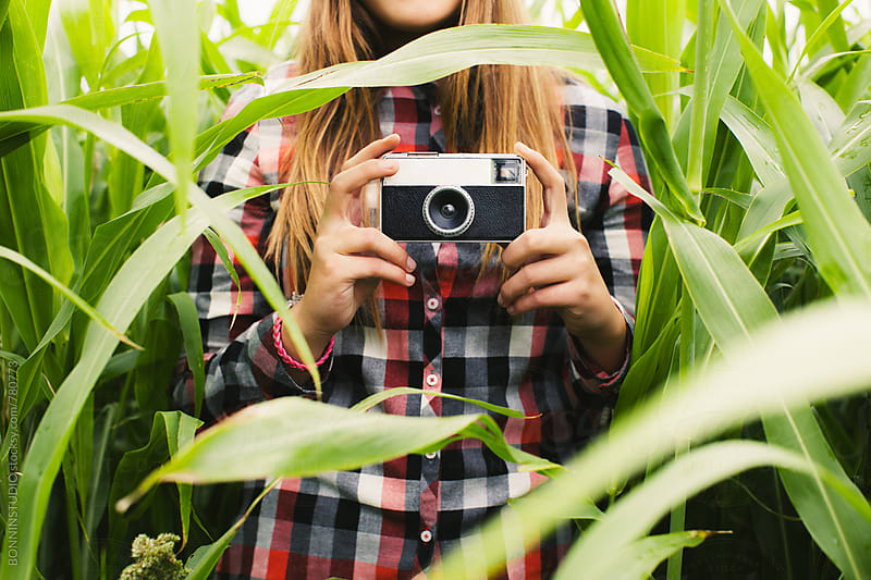 Anonymous teen girl holding an old camera in a corn field. by BONNINSTUDIO for Stocksy United
