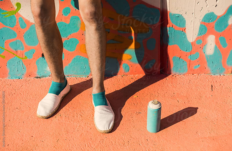 detail with legs and paint can with mural in background. by Marko Milanovic for Stocksy United
