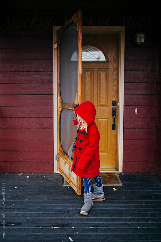 Side View of A Young Girl in A Red Coat Opening her Front Door by Amanda Voelker for Stocksy United