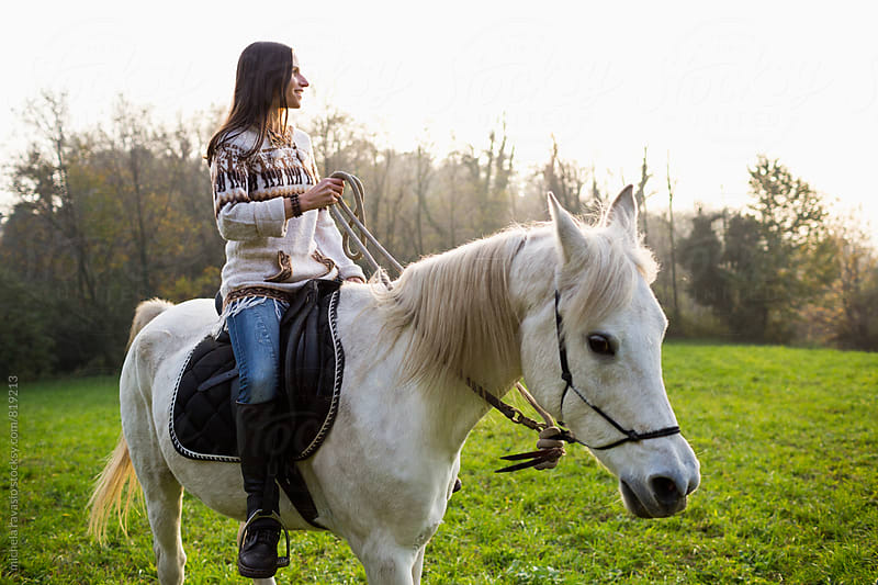 Young woman riding a white horse in nature by michela ravasio for Stocksy United