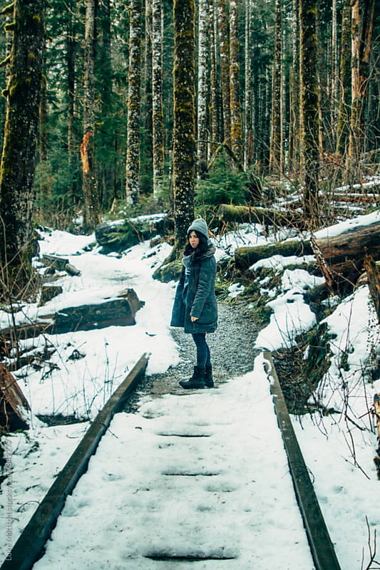 Young Brunette Woman Wearing Warm Clothes And Boots Standing On Snowy Forest Trail by Luke Mattson for Stocksy United