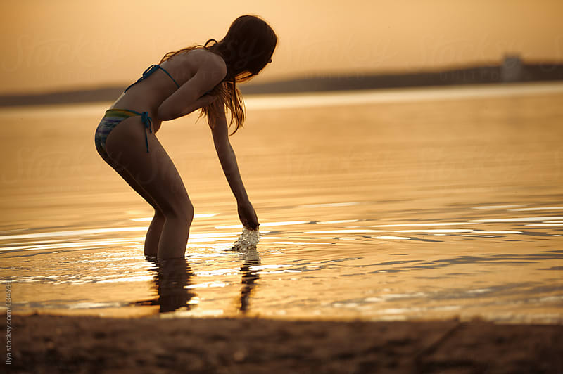 Young woman playing with water on the beach by Ilya for Stocksy United