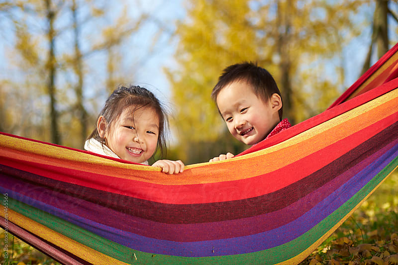 happy kids in rainbow boat by Bo Bo for Stocksy United