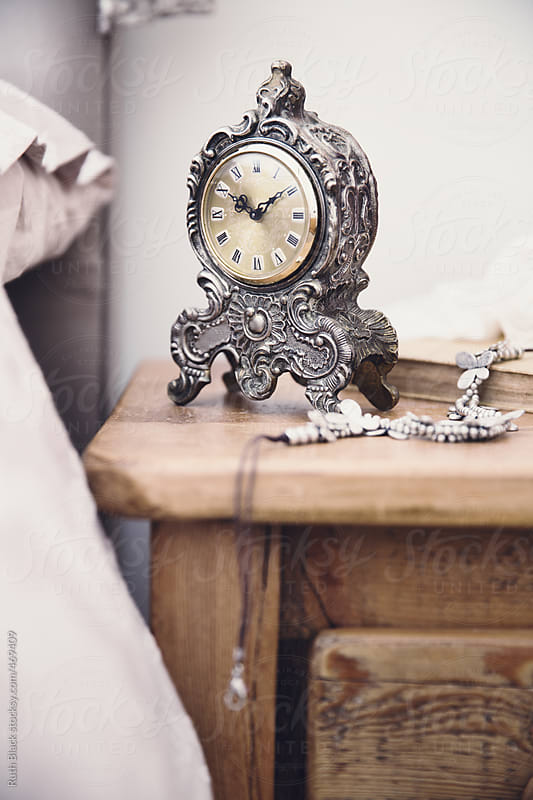 Wooden nightstand with vintage clock and jewellery by Ruth Black for Stocksy United