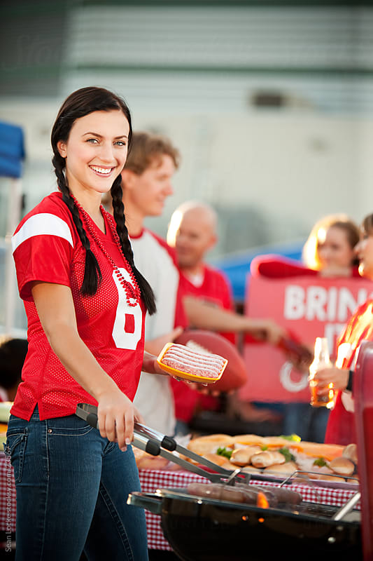 Tailgating: Woman Cooking Sausages on the Grill by Sean Locke for Stocksy United