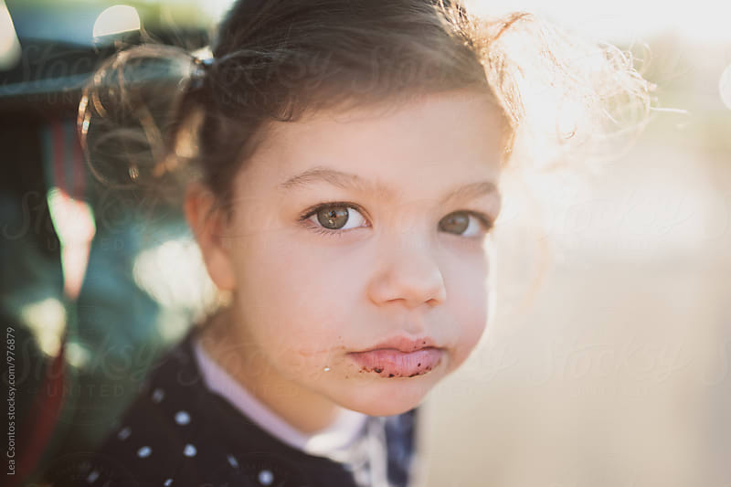 Portrait of a little girl with dirty, messy face by Lea Csontos for Stocksy United