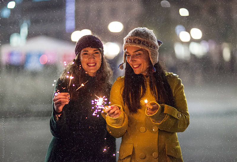 Friends Holding Sparklers on a Snowy Night by Mosuno for Stocksy United