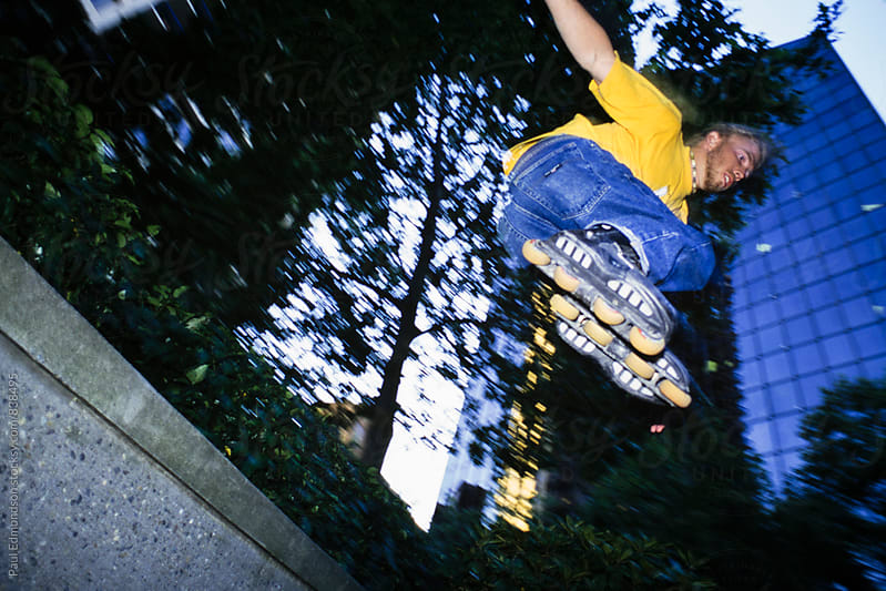 Man rollerblading and jumping over urban wall by Paul Edmondson for Stocksy United