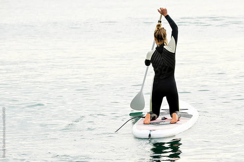 Blonde girl practicing paddle surf in Barcelona by Bisual Studio for Stocksy United