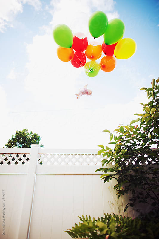 Baby Floats Over Fence by Kevin Russ for Stocksy United