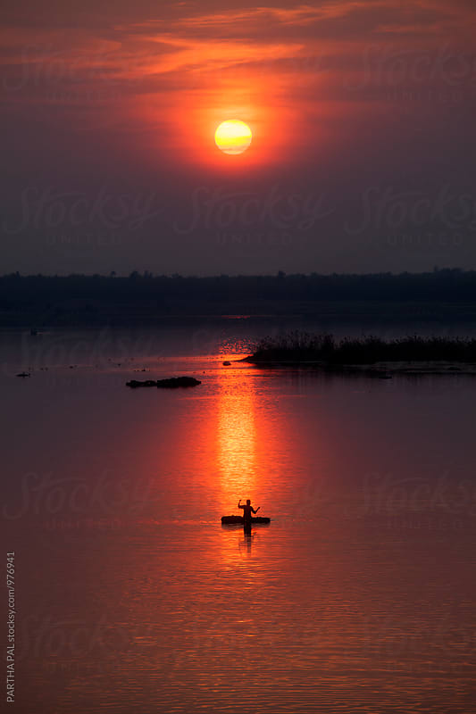 Fishermen with floating vessel in a lake at evening time by PARTHA PAL for Stocksy United