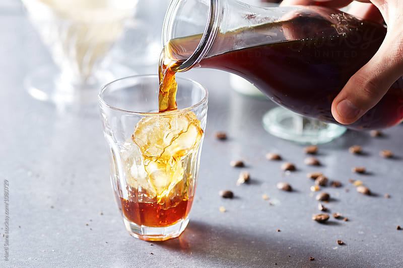 hand pouring black coffee in glass with ice by Martí Sans for Stocksy United