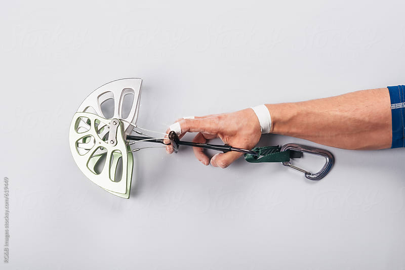 Male climber hand holding a camming device by RG&B Images for Stocksy United