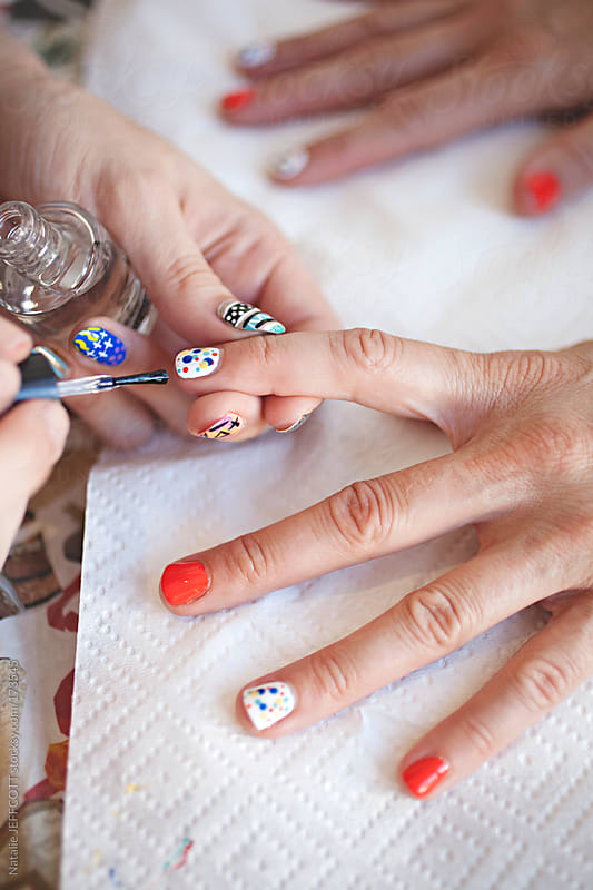 close up of lady's hand getting a colourful and spotty manicure / nail art by Natalie JEFFCOTT for Stocksy United