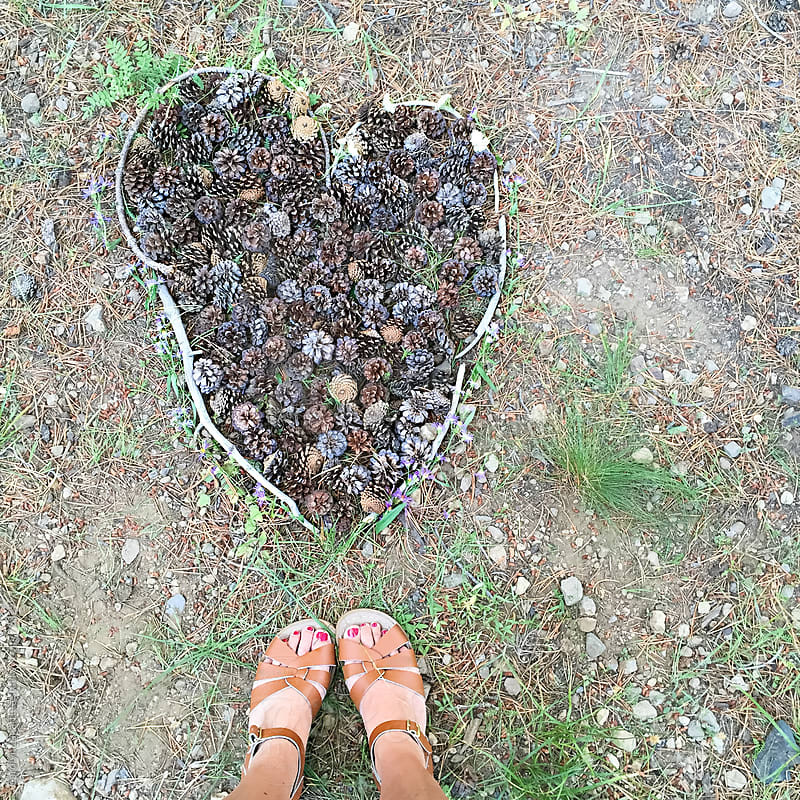 Feet standing above a heart made with sticks, pinecones and flowers by Carolyn Lagattuta for Stocksy United