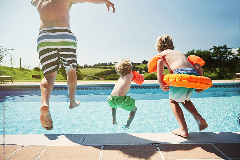 Father and two children jumping into a swimming pool by sally anscombe for Stocksy United