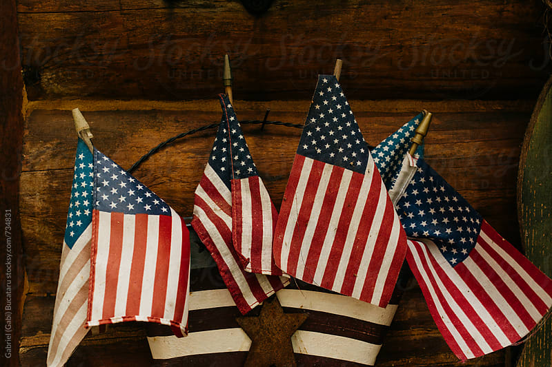 American flags on a log cabin wall by Gabriel (Gabi) Bucataru for Stocksy United