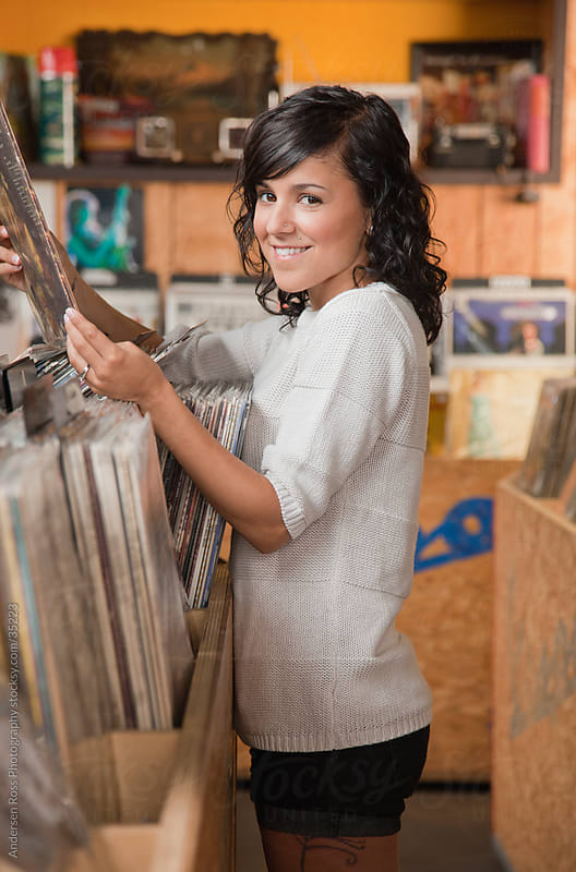 Portrait of young woman browsing records at record shop by Andersen Ross Photography for Stocksy United