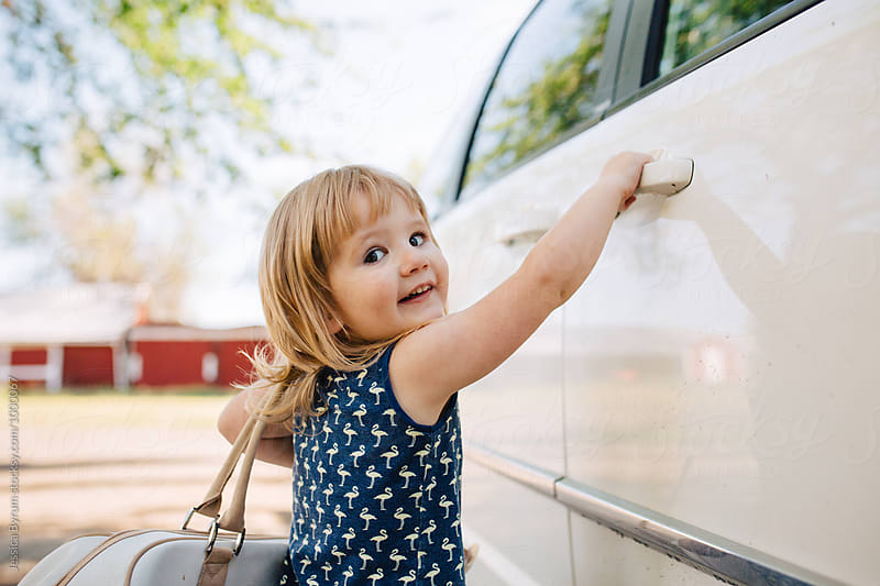 Toddler girl with a big bag opening a car door. by Jessica Byrum for Stocksy United