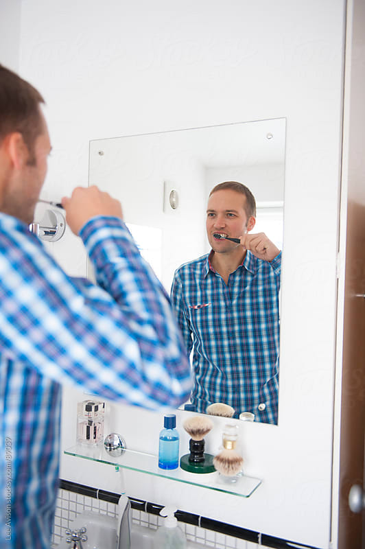 man brushing his teeth by Lee Avison for Stocksy United