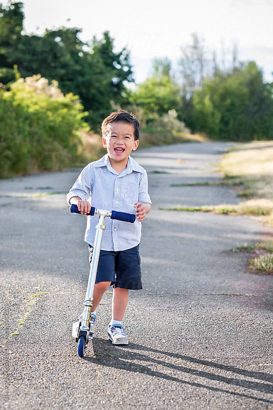 Happy Asian kid riding his scooter outdoor in a park by Suprijono Suharjoto for Stocksy United