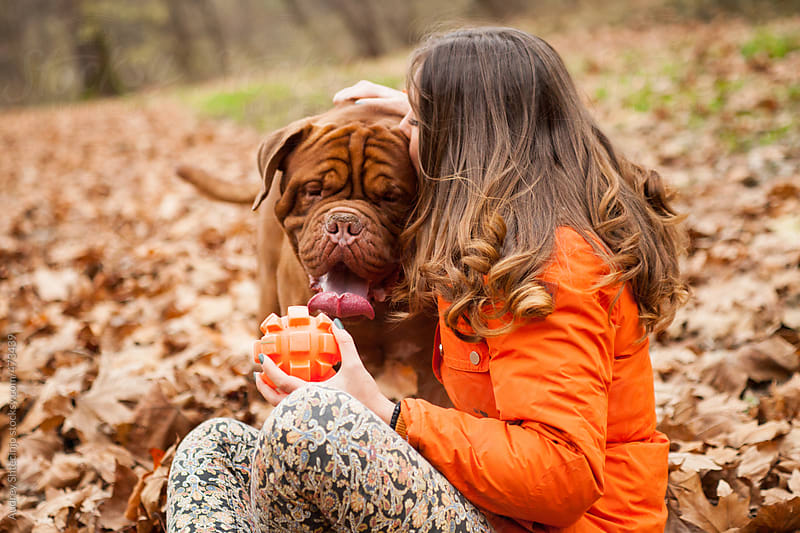 Girl kissing her pet while playing in park. by Audrey Shtecinjo for Stocksy United