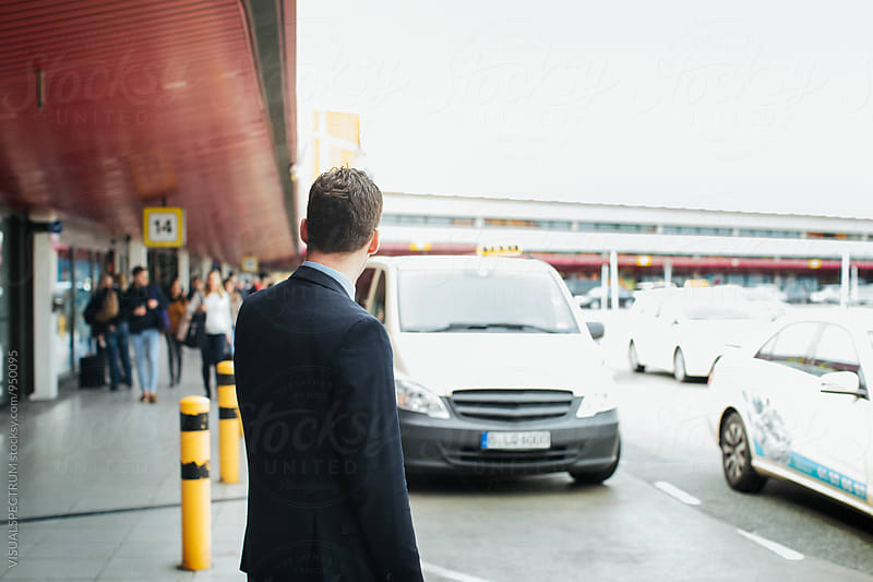 Young Caucasian Businessman Waiting For Taxi at Airport by Julien L. Balmer for Stocksy United