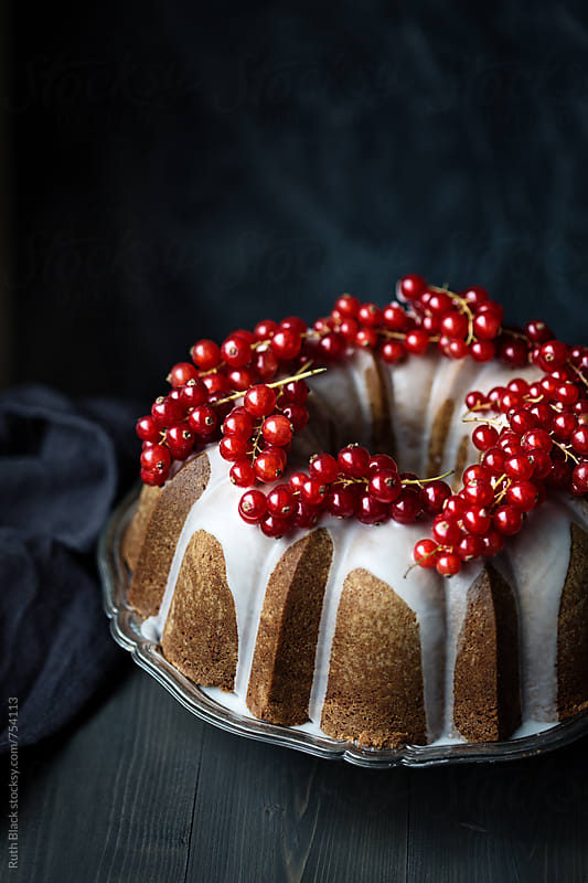 Iced bundt cake with redcurrants by Ruth Black for Stocksy United