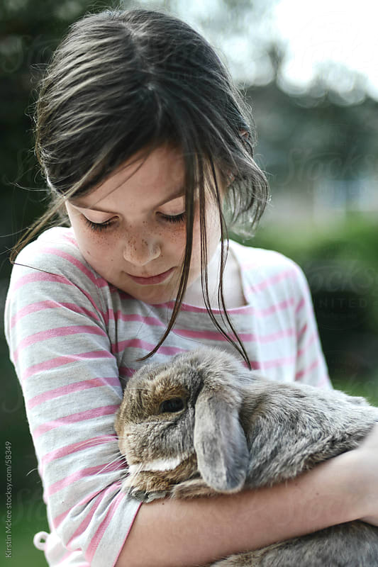 Girls gazes adoringly at a rabbit by Kirstin Mckee for Stocksy United