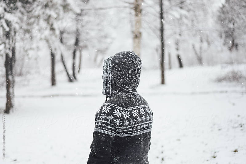 Person with winter sweater standing outdoors while snowing by Pixel Stories for Stocksy United