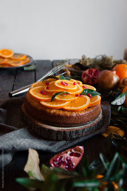 Orange cake on a wooden table by Nataša Mandić for Stocksy United