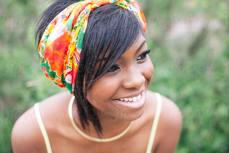 Close up of black girl smiling wearing head scarf by Gabrielle Lutze for Stocksy United