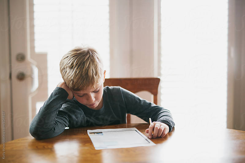 boy doing homework at the kitchen table  by Kelly Knox for Stocksy United