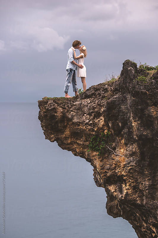Loving Couple Kissing  On The Rock With  Ocean View by Alexander Grabchilev for Stocksy United