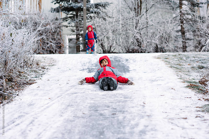 Boy slides down an icy path in winter while his brother watches, laughing by Tara Romasanta for Stocksy United